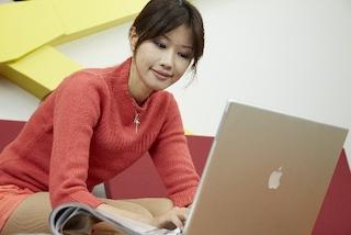 雑誌を見ながらMacを使っている若い女性