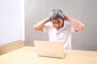 パソコンの前で頭をかかえる男