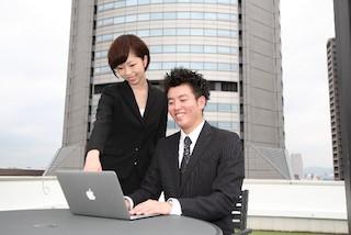 Macを使っている若いビジネスマン男女