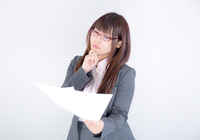 書類を眺めながら考えこむ女性